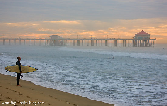 A surfer checking out the early morning waves, Huntington Beach, California.