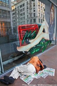 A homeless person sleeps on a sidewalk in downtown San Francisco, California.