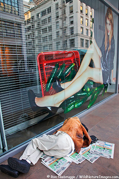 A homeless person sleeps on a sidewalk in downtown San Francisco, California.