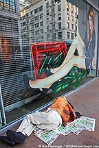 A homeless man sleeps in front of a photo of a glamorous model, San Francisco, California.