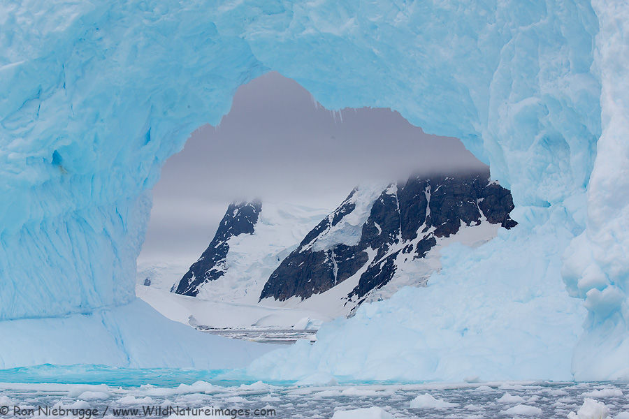 Arch in a large iceberg near Petermann Island, Antarctica.